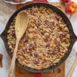 Peach crisp in cast iron skillet with wooden spoon.