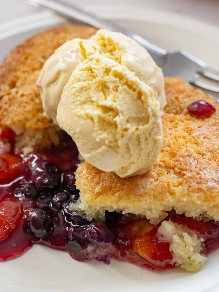 Close up image of peach and blueberry cobbler with vanilla ice cream.