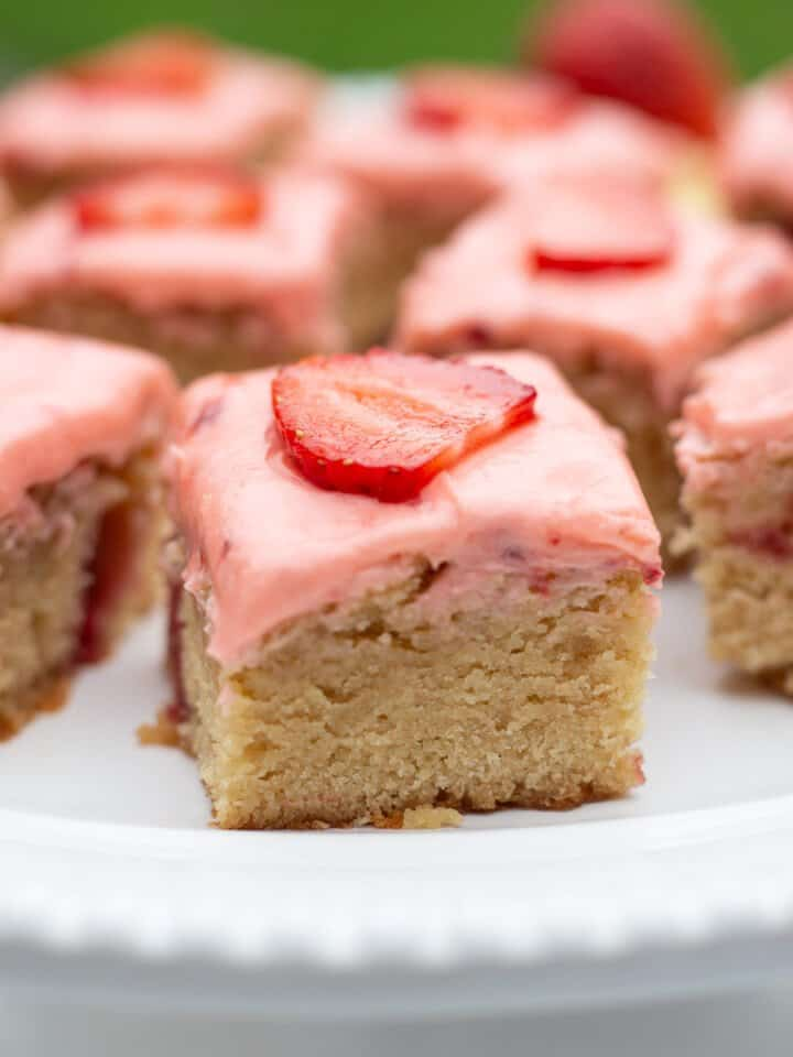 Close up image of strawberry lemon blondies on white plate.