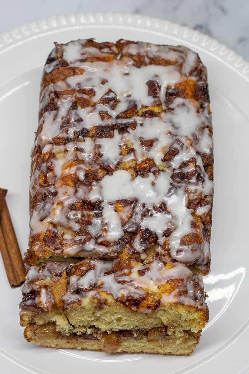 Apple Fritter Loaf Cake with glaze drizzled on top on white plate.