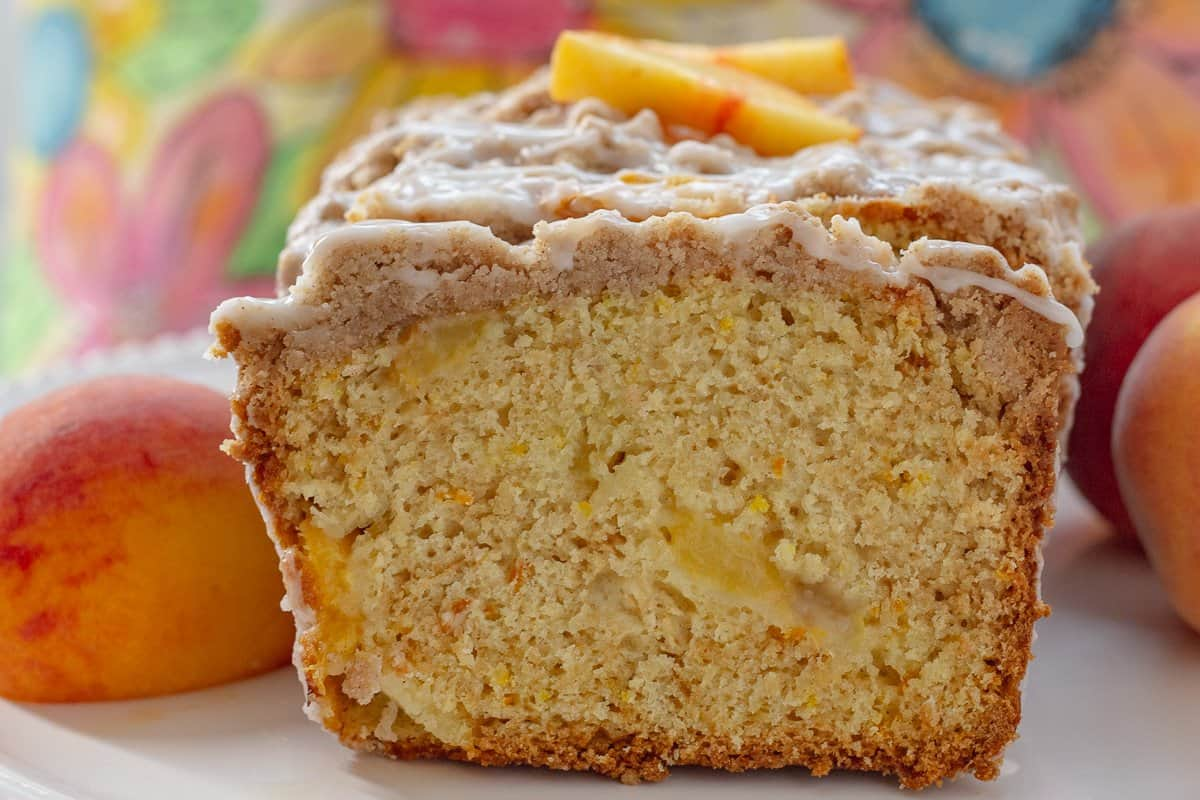 Peach Cobbler Pound Cake with one slice cut from it with fresh peaches  beside the cake.