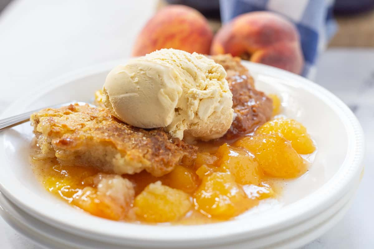 Two scoops of vanilla ice cream on top of peach cobbler on white plate with fork.
