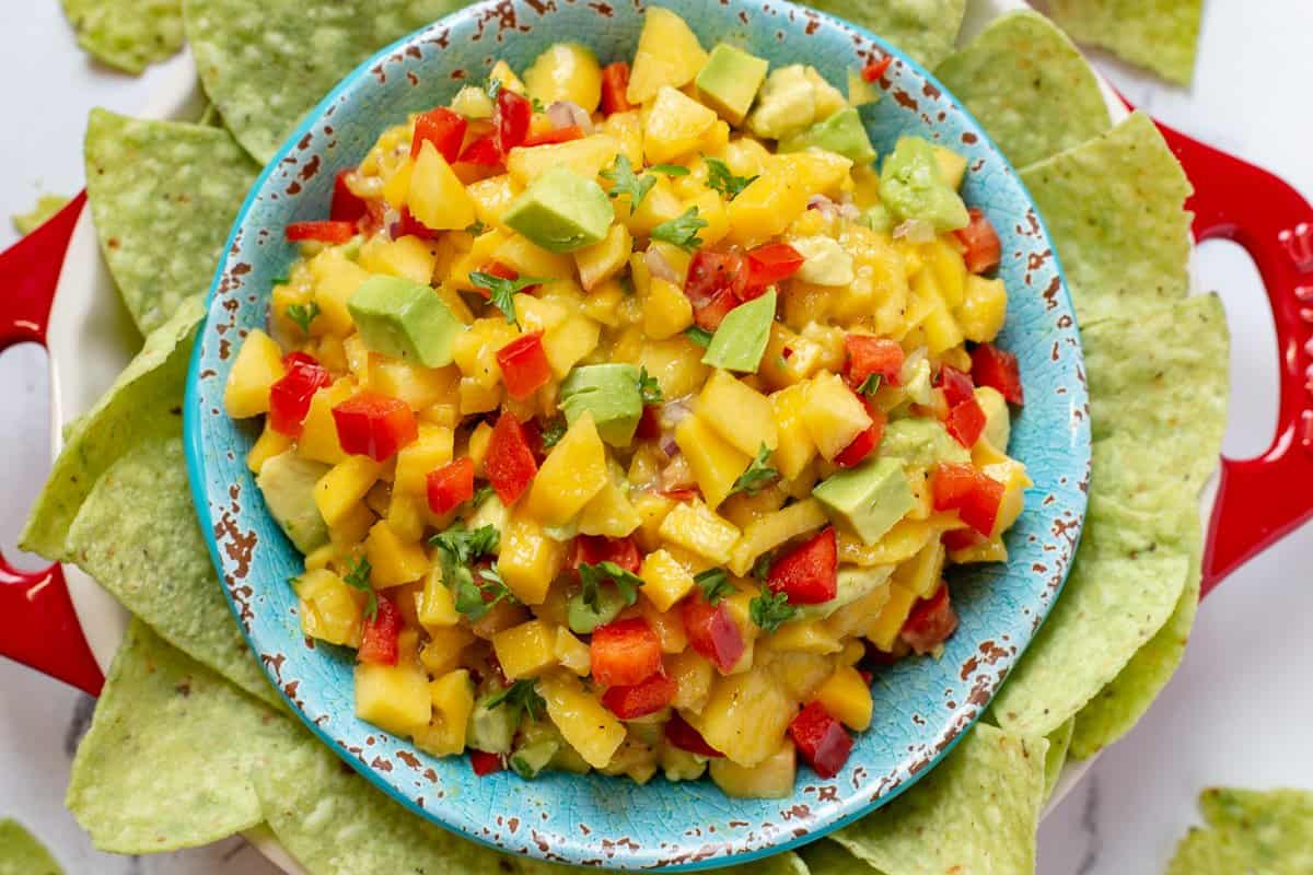 Overhead image of peach mango salsa in blue bowl surrounded by nachos.