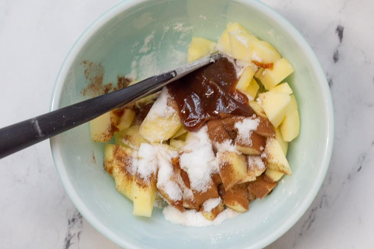 Apples, apple butter, sugar and cinnamon in mixing bowl with spoon.