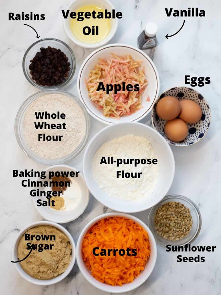 Ingredients for bakery style morning glory muffins in salt bowls with text overlay.