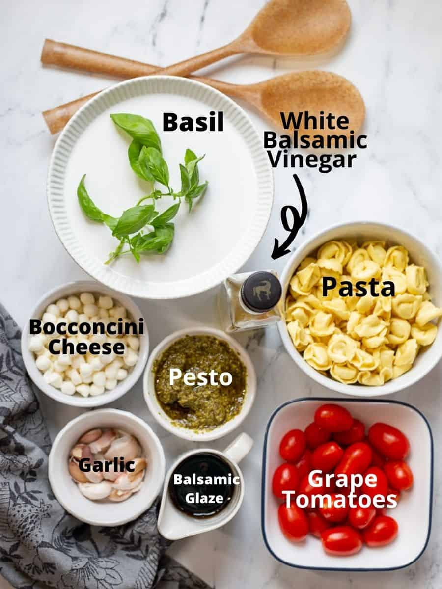 Ingredients for caprese pesto Pasta Salad in glass bowls with text overlay.