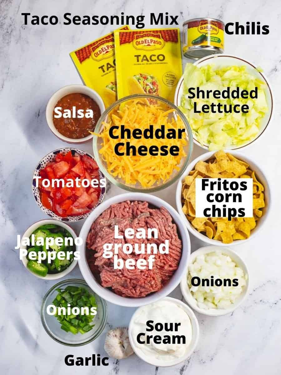 Ingredients for walking taco casserole in glass bowls with text overlay.