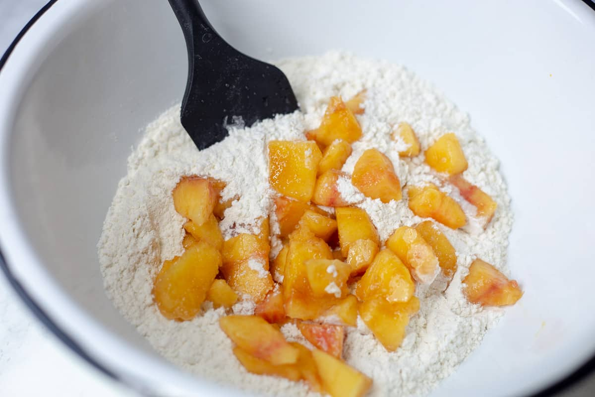 Peaches are added to dry ingredients in mixing bowl with spoon.