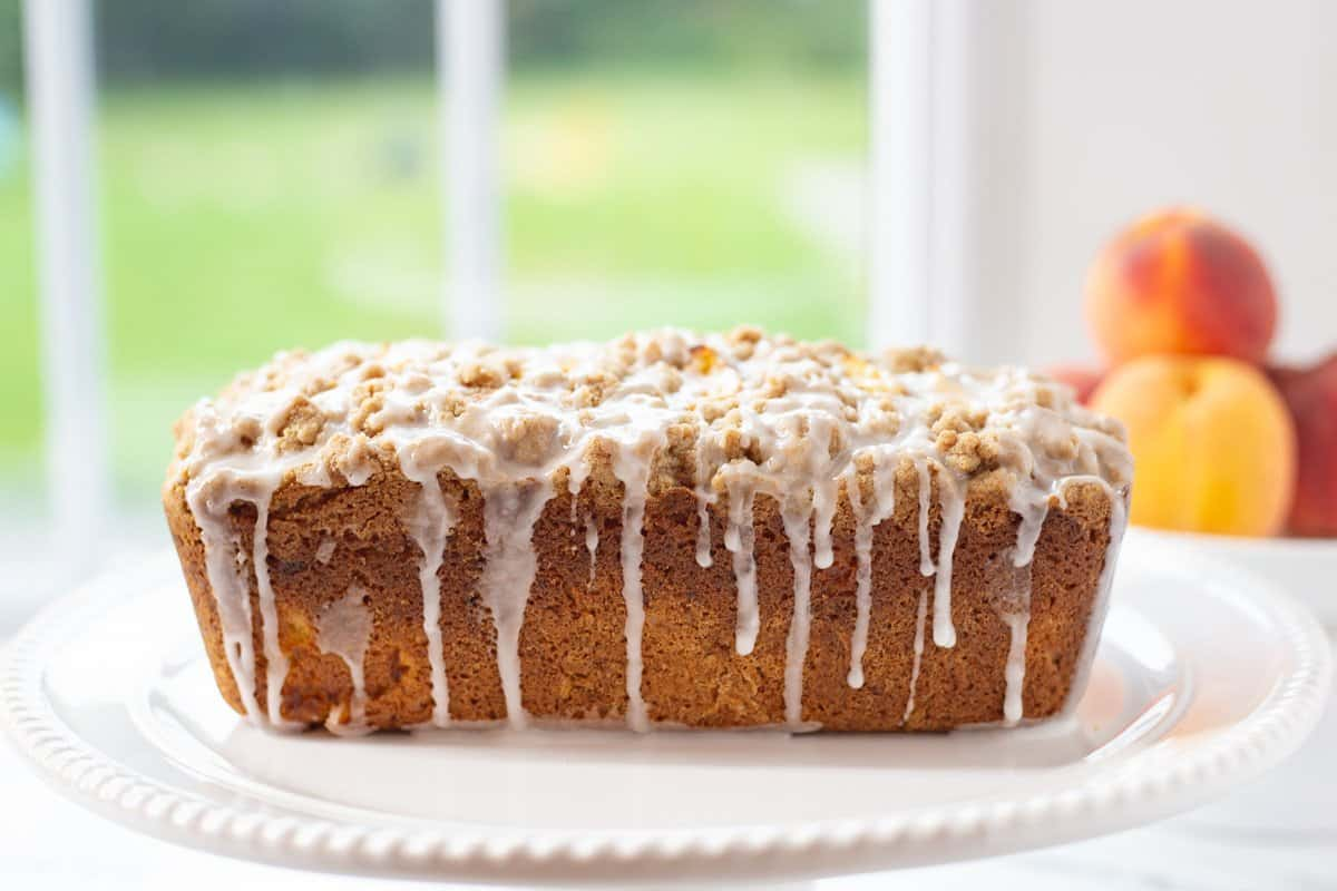 Peach Cobbler Pound Cake is drizzled with glaze sitting on a white plate with fresh peaches in the background.