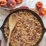 Baked Peach Crisp in cast iron skillet with wooden spoon.