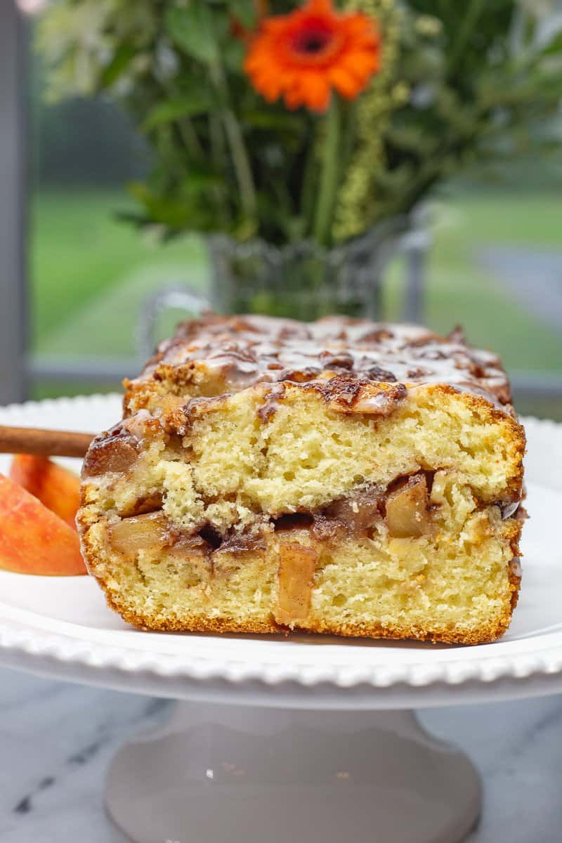 Sliced Apple Fritter Bread on white plate with flowers in the background.
