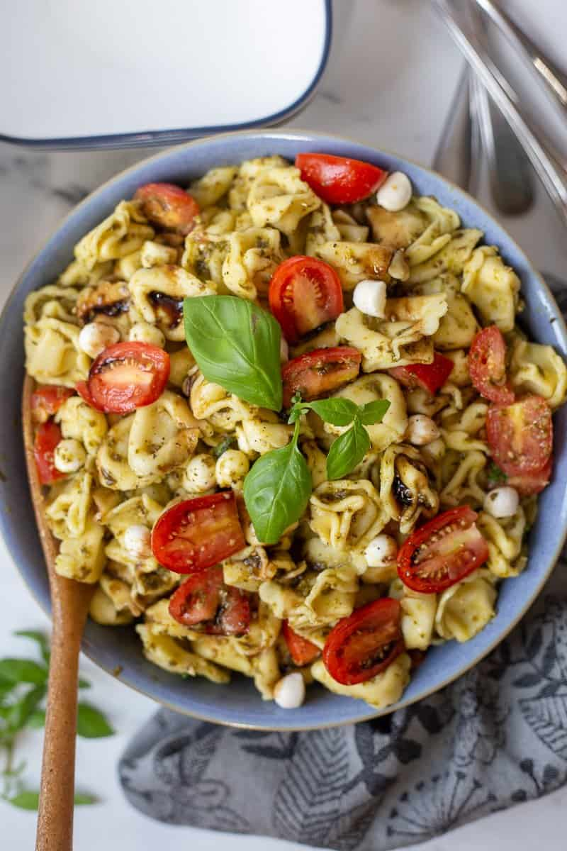 Caprese Pesto Pasta Salad in blue bowl with balsamic glaze drizzled on top.