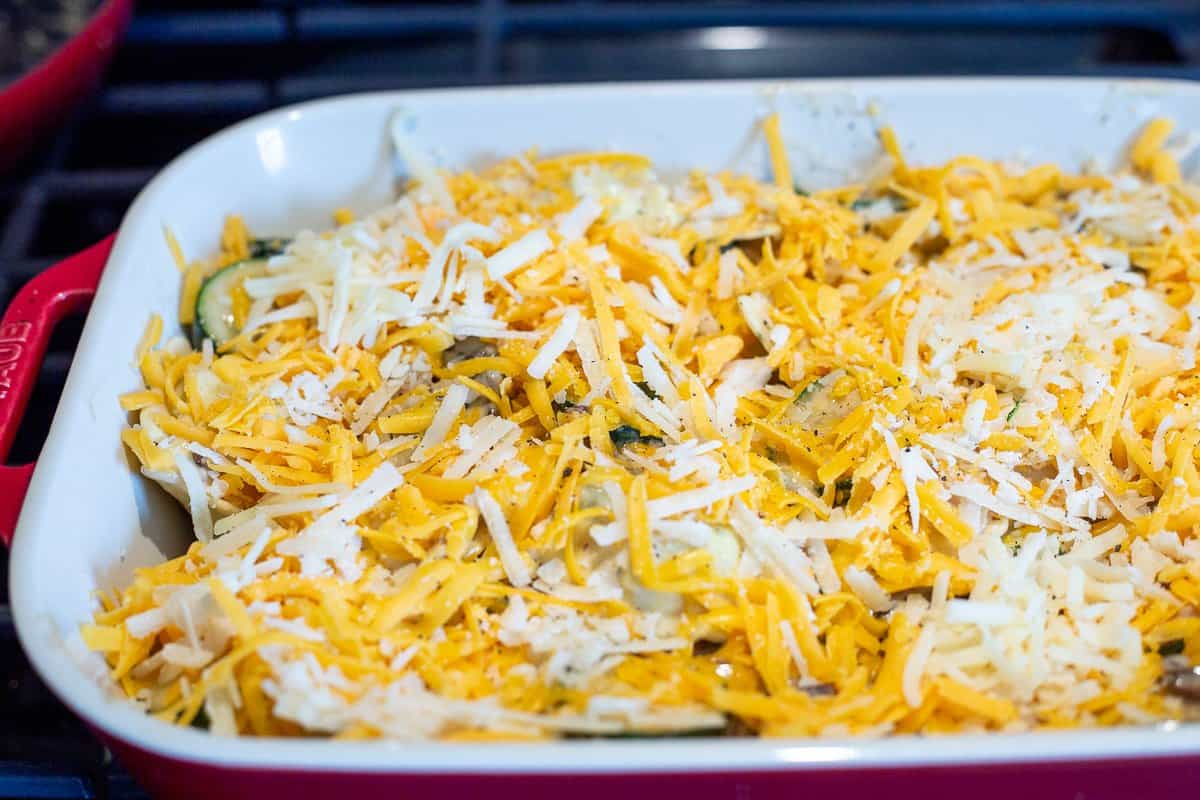 Unbaked Ravioli Alfredo in baking dish with shredded cheese on top.