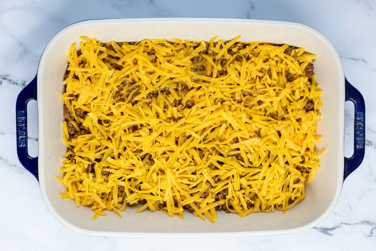 Shredded cheese is added to the ground beef mixture in baking dish.