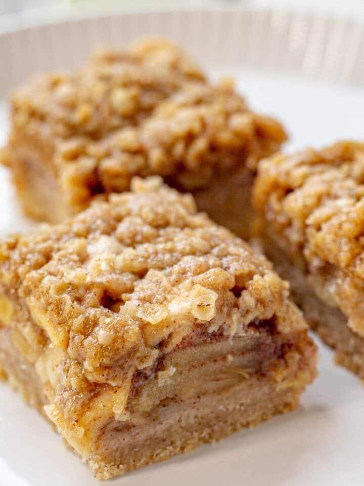Apple pie bars on white plate.
