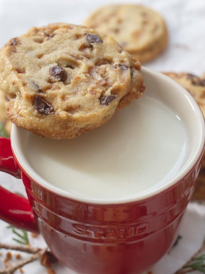 Chocolate chip toffee icebox cookie sitting on a red cup with milk in it.