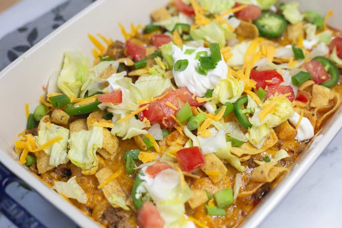 Walking Taco Casserole with shredded lettuce, tomatoes, sour cream and cheese.