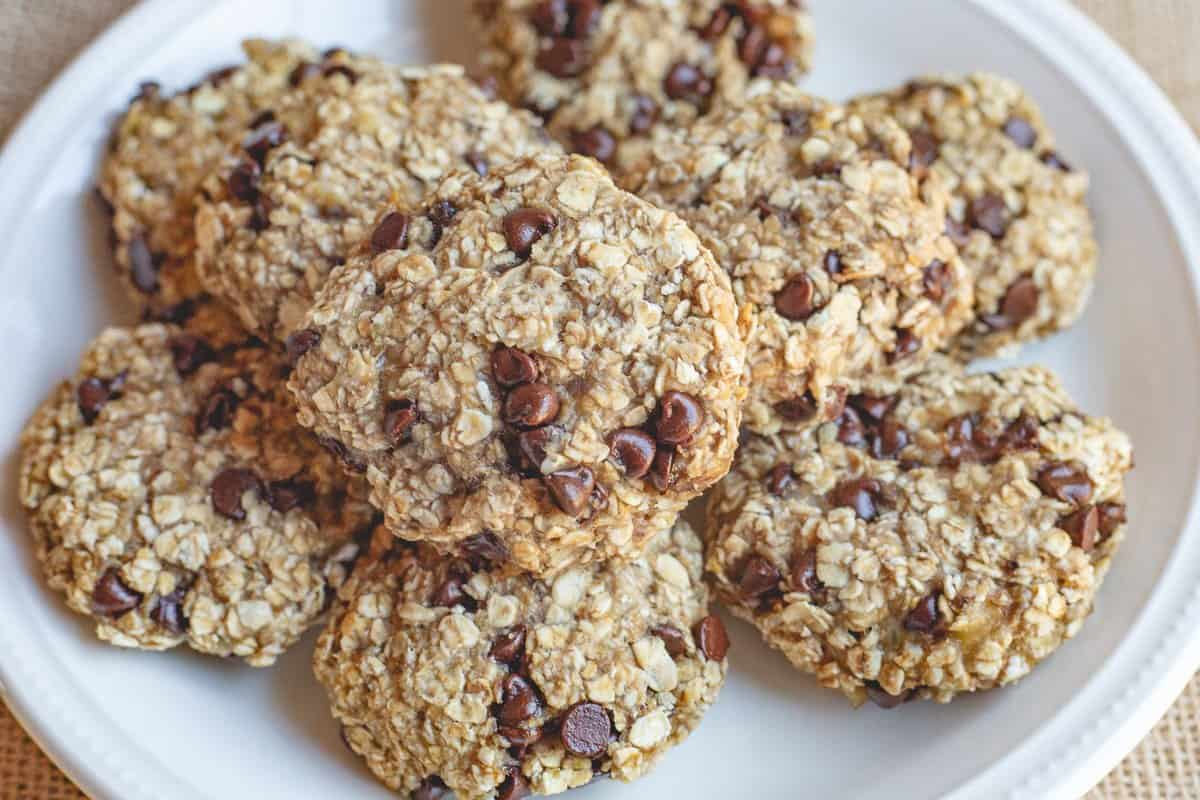 Several banana oatmeal breakfast cookies with chocolate chips on a white plate.