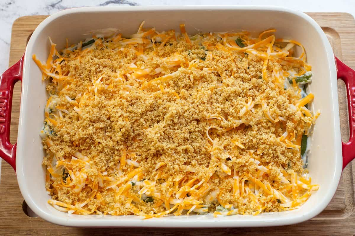 Breadcrumbs are sprinkled on top of shredded cheese on top of green bean casserole.