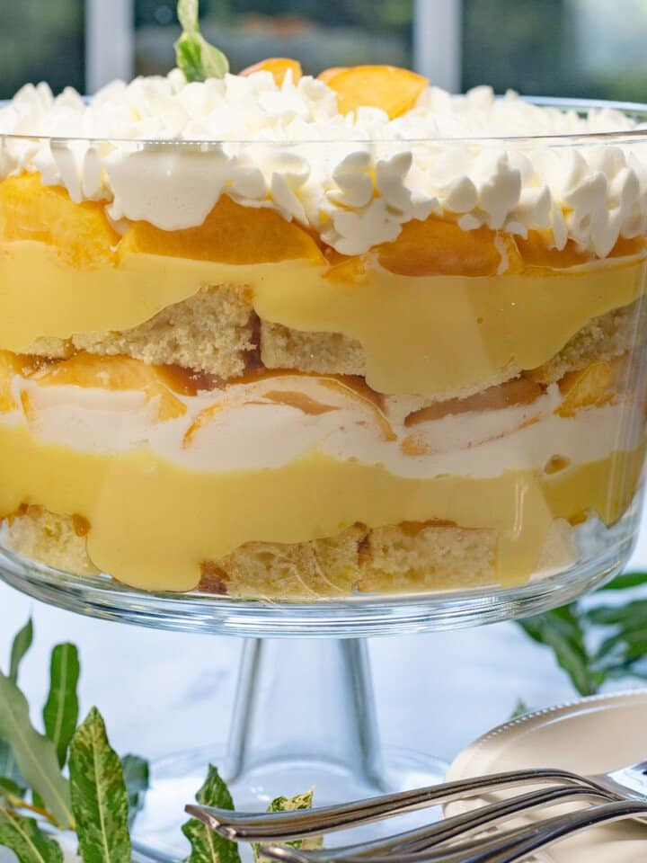 Close up image of fresh peach trifle in glass trifle bowl.