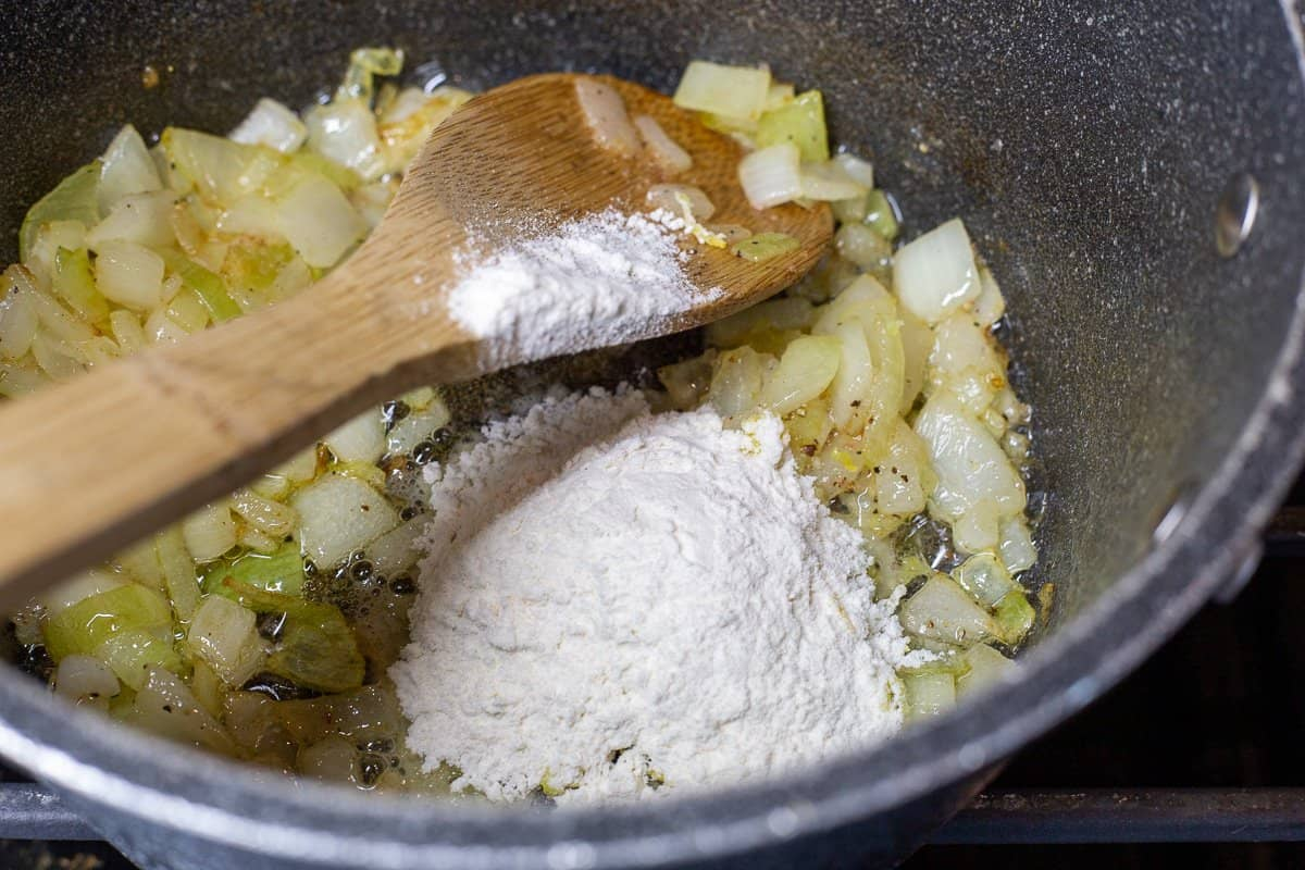 Flour and lemon zest is added to the onion mixture in saucepan.