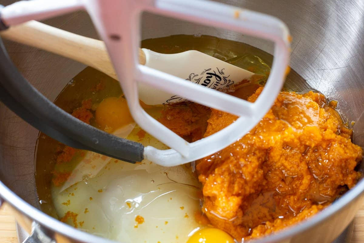 Pumpkin, oil, eggs and sugar in mixing bowl of stand mixer with spatula.