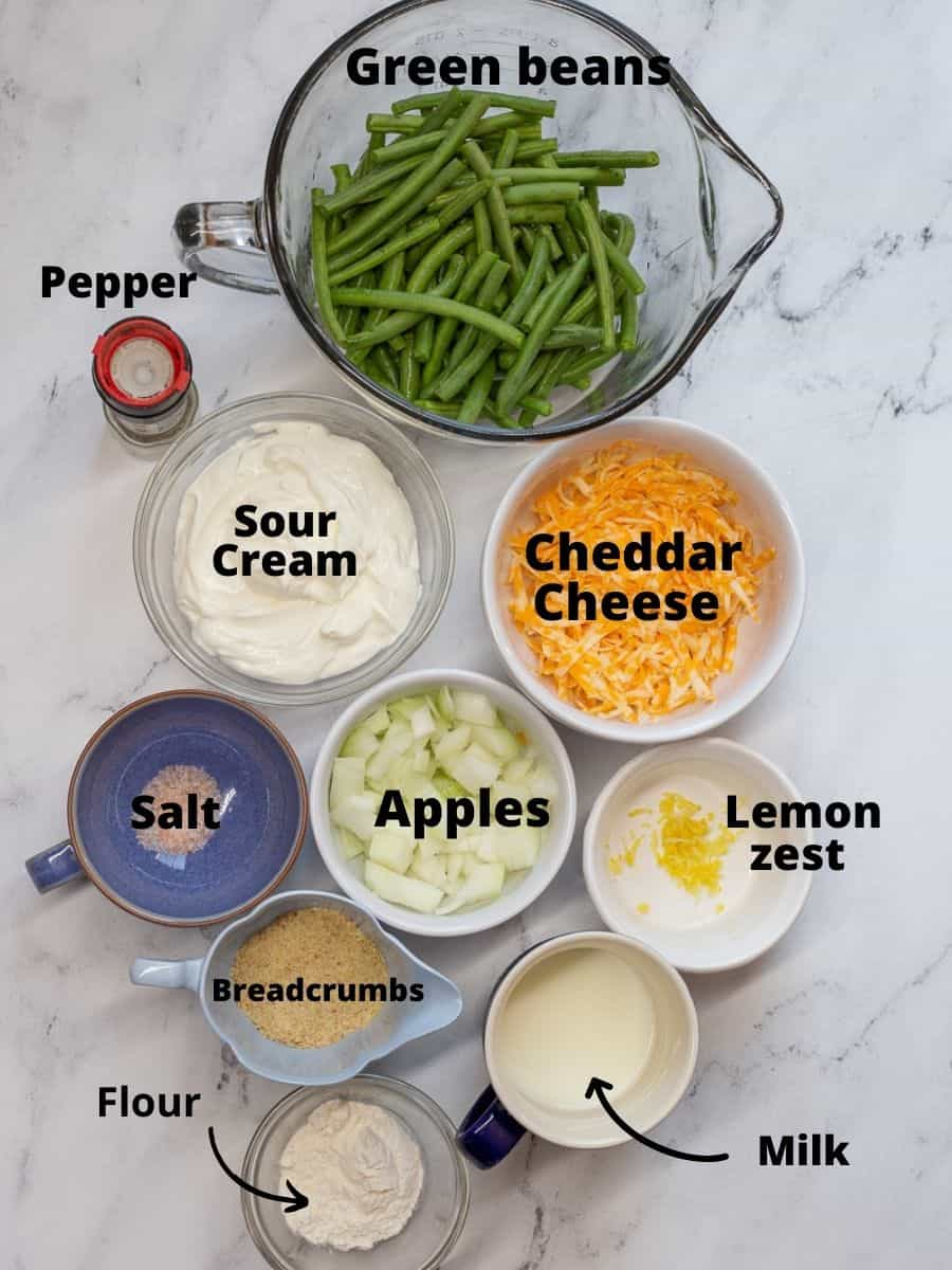 Ingredients for green bean casserole in glass dishes with text overlay.