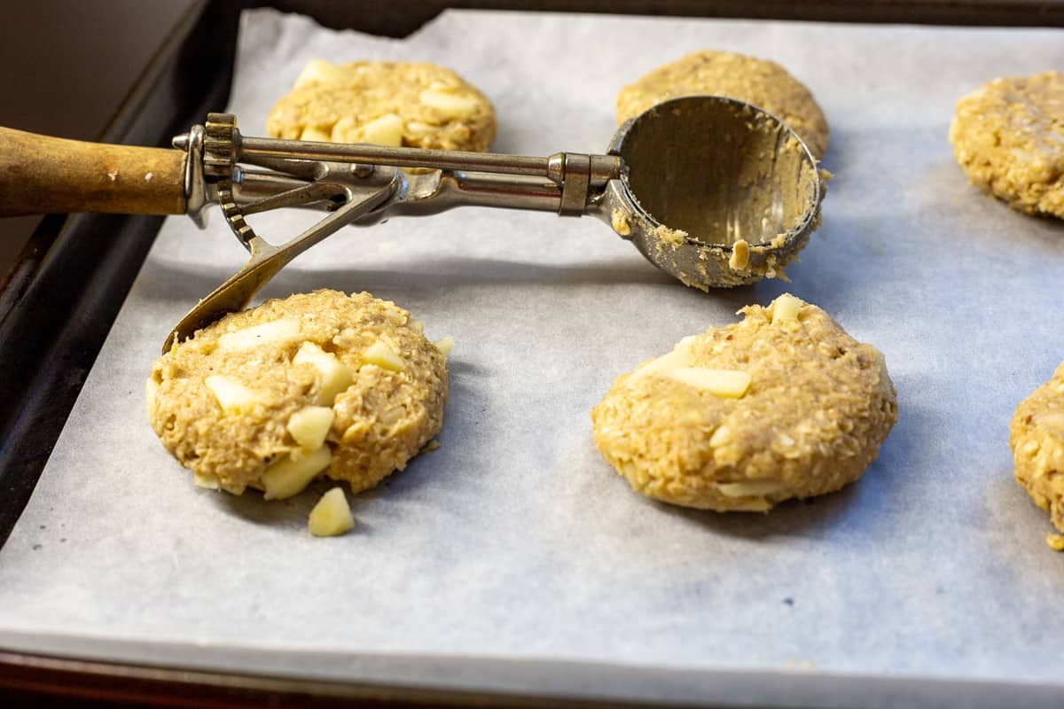 Unbaked cookies on parchment-lined baking sheet with ice cream scoop.