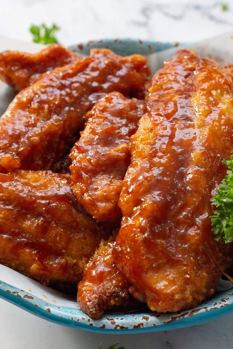 Close up image of baked bbq chicken tenders in blue bowl with parsley.