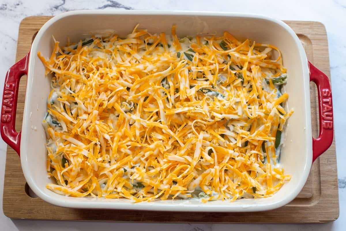 Shredded cheese is sprinkled on top of green bean mixture in red casserole dish.