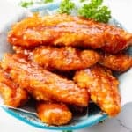 Baked bbq chicken tenders in blue bowl with parsley.