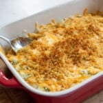 Green Bean Casserole in red baking dish with spoon.