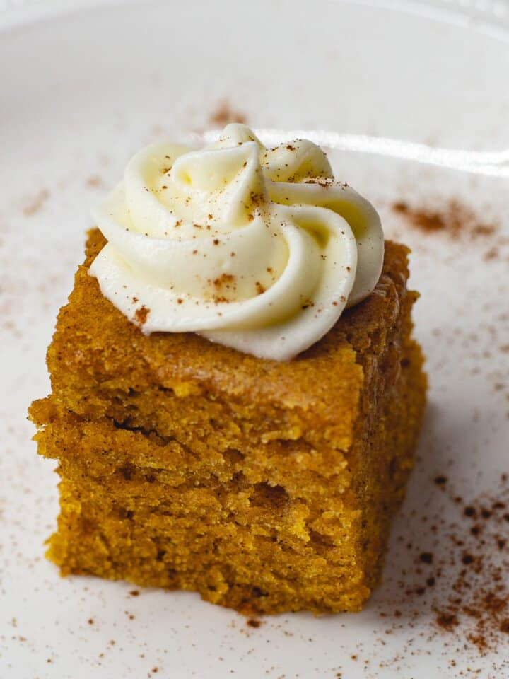 Pumpkin bars with cream cheese frosting on white plate.